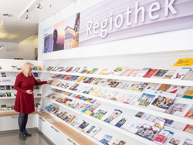 Regiothek – Frau an Magazin-Auswahl-Regal
