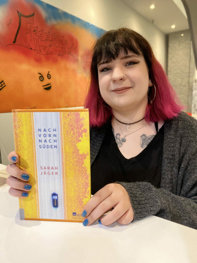 Junge Frau hält ein Buch und lacht