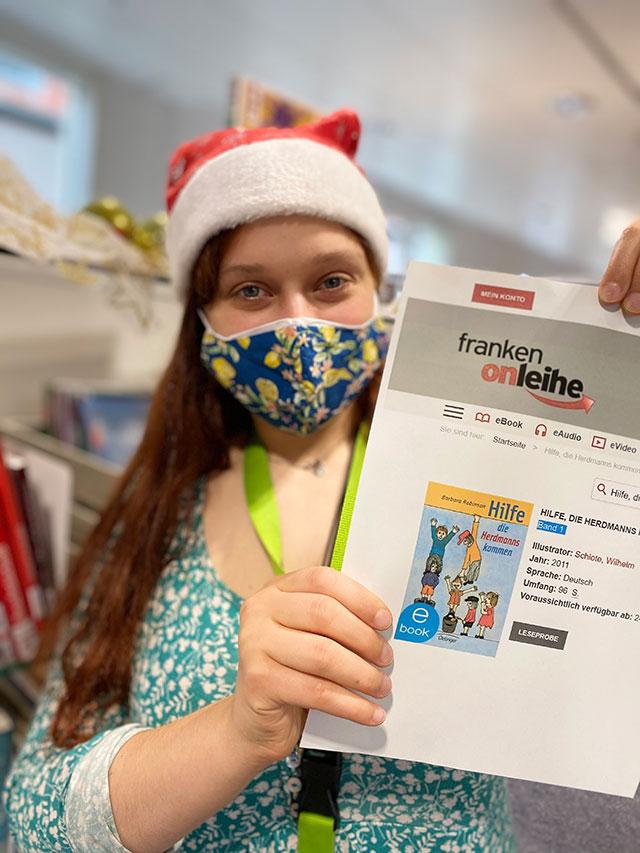 Junge Frau mit Weihnachtsmütze und Mundschutz hält Zettel hoch