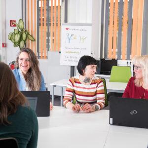 Mehrere Frauen lernen gemeinsam und reden vor Laptops