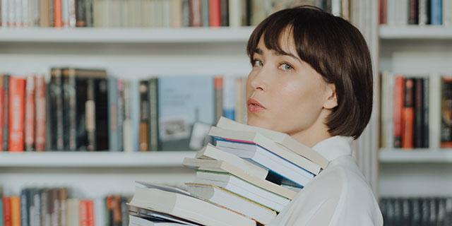Junge Frau trägt einen Stapel Bücher
