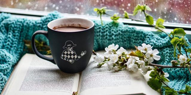 Tassse mit heißer Schokolade die auf einem aufgeschlagenen Buch steht