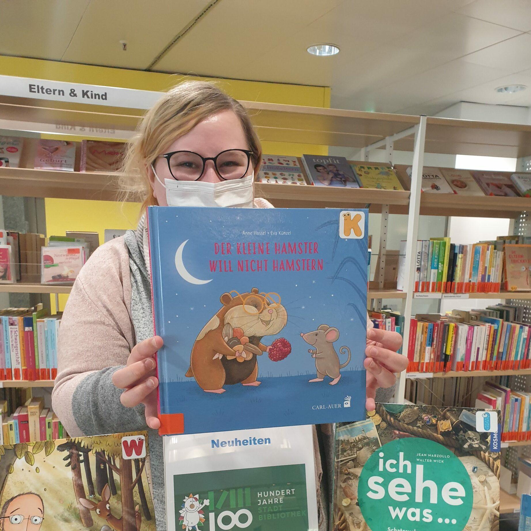 Junge Frau hält das Buch der kleine Hamster will nicht hamstern