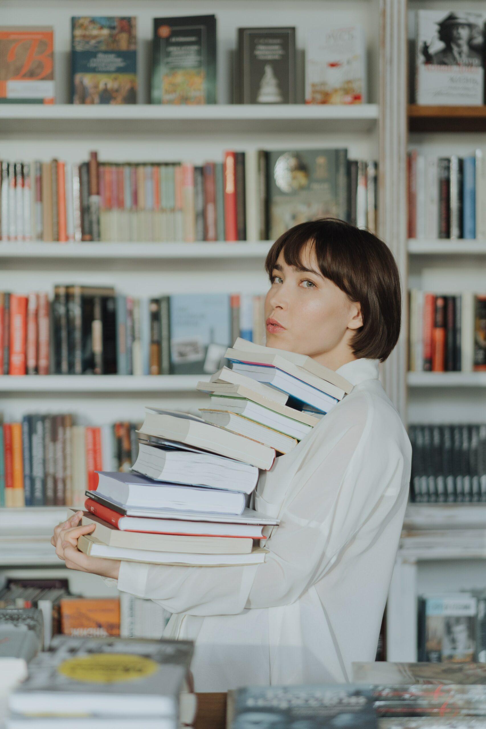 Junge Frau trägt einen Stapel Bücherer