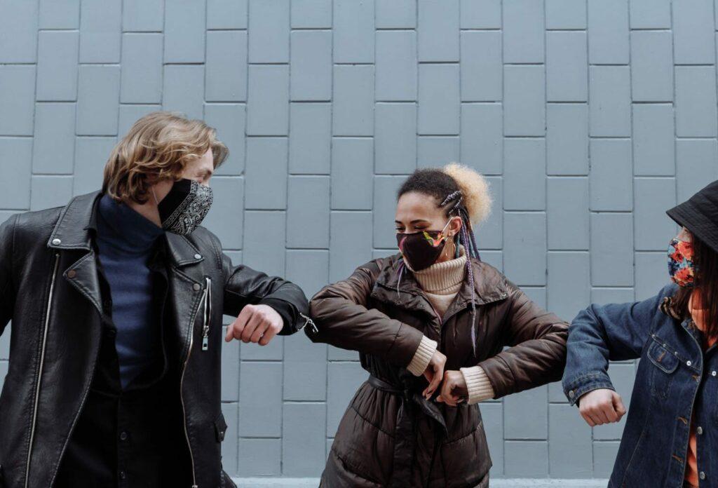 Junge Menschen mit Maske begrüßen sich mit Ellebogen