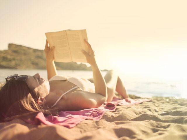 Frau am Strand mit Buch