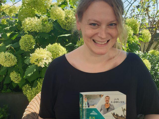 Frau lacht mit Buch in der Hand