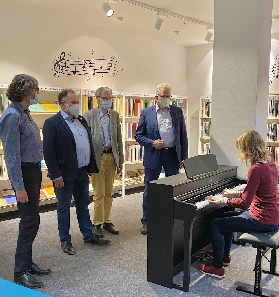Vier Männer stehen um ein E-Piano und eine junge Frau spielt darauf
