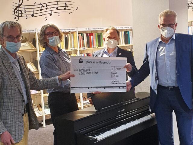 4 Männer halten einen Scheck und freuen sich.